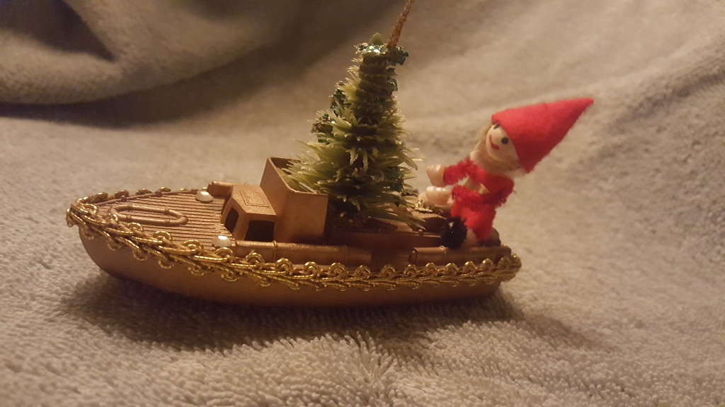 Photograph of elf in gold plastic boat with bottle brush tree in boat.